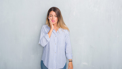 Young adult woman over grey grunge wall wearing fashion business outfit touching mouth with hand with painful expression because of toothache or dental illness on teeth. Dentist concept.