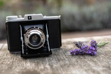 Antike Kamera in der Hülle mit Riemen liegt draußen auf dem Tisch daneben liegt ein Sträußchen Lavendel