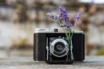 Vintage Kamera steht auf dem Holztisch mit Sträußchen Lavendel