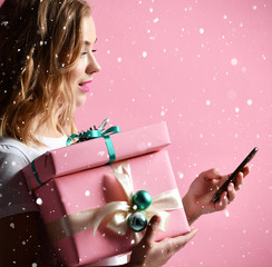 woman shopping online with mobile cellphone for christmas presents gifts smiling on light pink