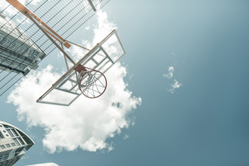 Basketball game. Low angle of a basketball basket handing against a blue sky
