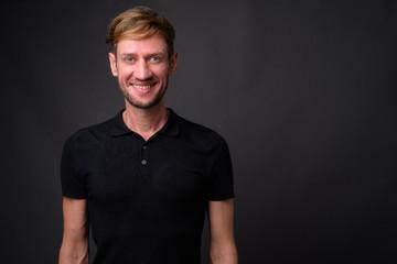 Studio shot of blond bearded man against gray background