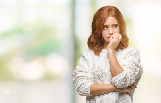 Young beautiful woman over isolated background wearing winter sweater looking stressed and nervous with hands on mouth biting nails. Anxiety problem.