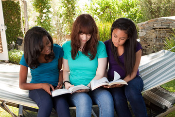 Diverse group of teenage girls reading outside.