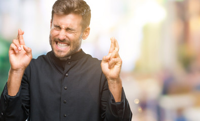 Young catholic christian priest man over isolated background smiling crossing fingers with hope and eyes closed. Luck and superstitious concept.