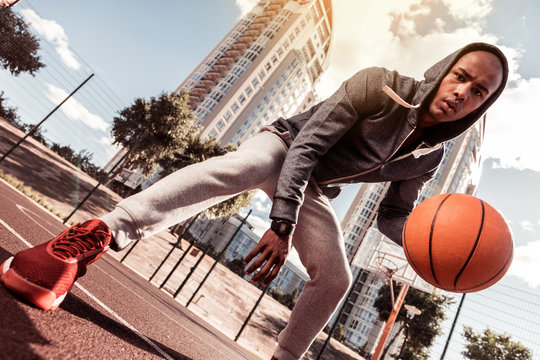 Sportive youth. Low angle of a nice young man looking at you while playing basketball
