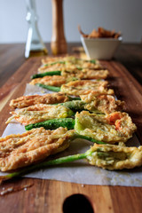 Fried zucchini squash courgette flowers on a wooden table. Italian appetiser.