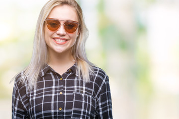 Young blonde woman wearing sunglasses over isolated background with a happy and cool smile on face. Lucky person.