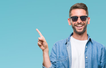 Young handsome man wearing sunglasses over isolated background with a big smile on face, pointing with hand and finger to the side looking at the camera.