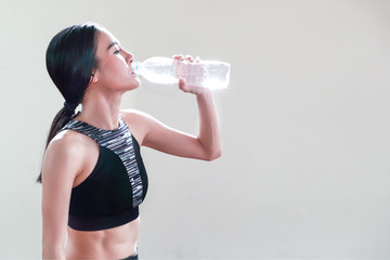 young healthy and sporty woman drinking water in gym