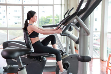 portrait of young healthy and sporty woman bicycling on exercise machine in gym