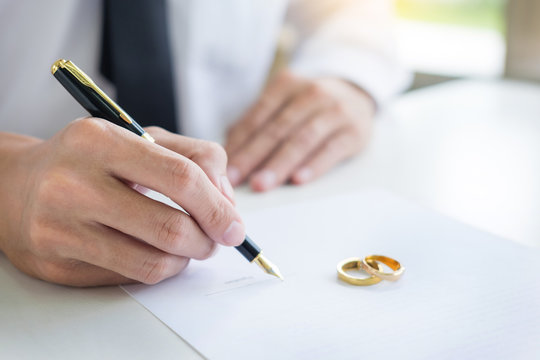 Closeup of a man Signing Contract or premarital agreement, filling petition form agreement of divorce in office at lawyer desk in court room  Conceptual of marriage