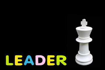 """Alphabet sponge rubber of text """"LEADER"""" with chess king standing isolated over black background. Business and leader concept."""