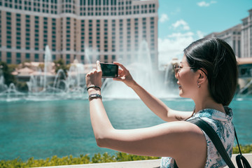 young girl traveler take pictures of fountain