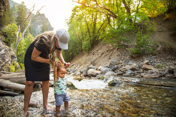 Woman and child hiking across a beautiful scenic mountain river. Walking in the mountain stream on a warm summer day together. lifestyle photo of a mother and her son in the outdoors Fotoväggar