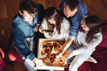 Group of happy friends at home party. Eating pizza together. Asian woman taking picture of the the slice to share memory. Top view