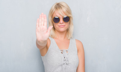 Adult caucasian woman over grunge grey wall wearing retro sunglasses with open hand doing stop sign with serious and confident expression, defense gesture