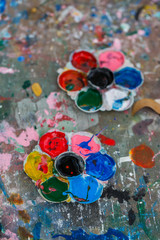 Photo of a artists palette loaded with various colour paints