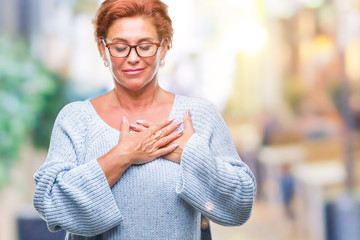 Atrractive senior caucasian redhead woman wearing glasses over isolated background smiling with hands on chest with closed eyes and grateful gesture on face. Health concept.