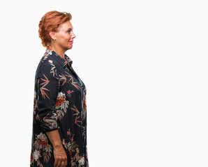 Atrractive senior caucasian redhead woman over isolated background looking to side, relax profile pose with natural face with confident smile.