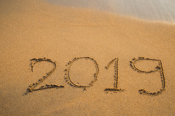 Abstract message Year 2019 written on beach sand