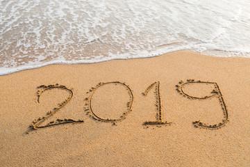 Abstract message Year 2019 written on beach sand
