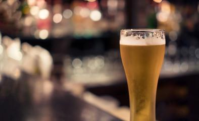 Pilsner beer glass with bar background