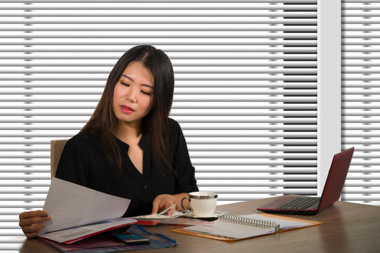 company corporate portrait of young beautiful and busy Asian Chinese woman working busy at modern office computer desk by venetian blinds window in business lifestyle