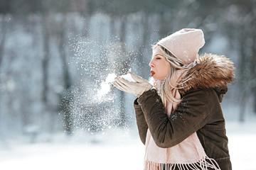 Beautiful young woman enjoying in the snow