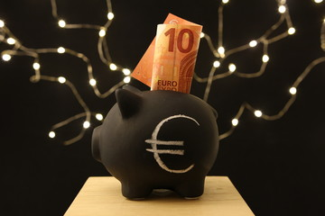 Saving money - black piggy banks with 10 EURO on black background with lightings