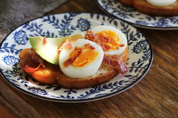 Bruschetta with avocado, chrispy bacon and egg served on plate