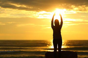 Woman reaching sun at sunset on the beach