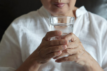 elderly woman are  eating medicine and with pills and glass of water at home
