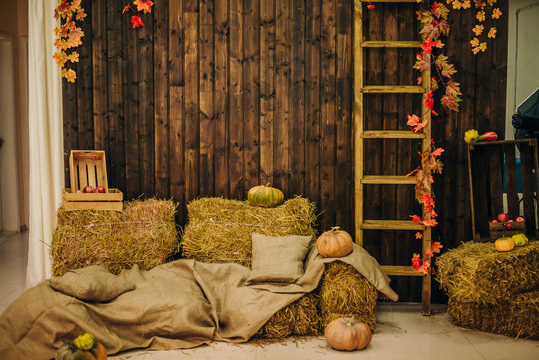 hay bales and pillows. rustic style area. Scenery for photo shoots. Wooden wall. Autumn background