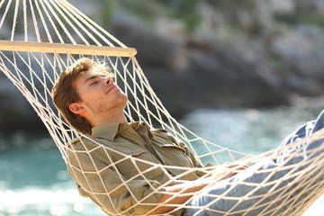Relaxed man sleeping on a hammock on vacation