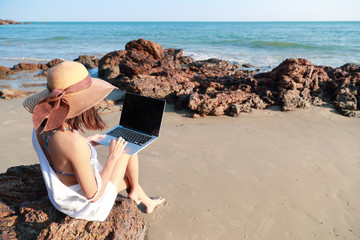 beautiful and cute businesswoman using laptop computer with sun glasses and hat on the beach during holiday vacation
