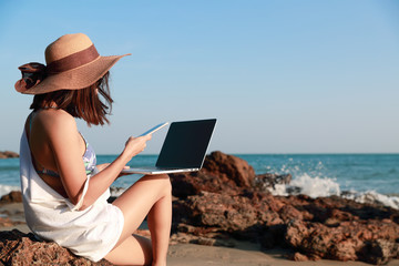 beautiful and cute businesswoman using laptop computer and cell phone with sun glasses and hat on the beach during holiday vacation