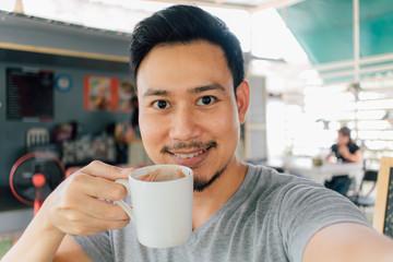 Selfie portrait of happy man drink mug of hot coffee.