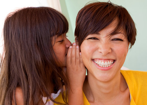 Mother and daughter smiling and telling secrets.