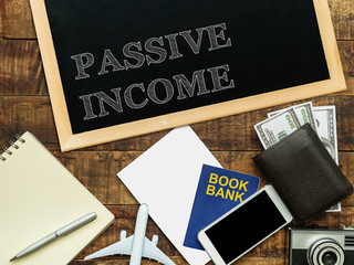 passive income, financial concept. text PASSIVE INCOME on chalkboard at the wooden table with book bank , money wallet , banknote , mobile phone , plane model and camera