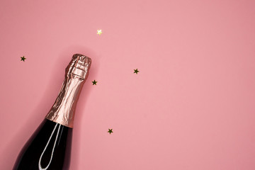 champagne bottle and confetti, flat lay, copy space
