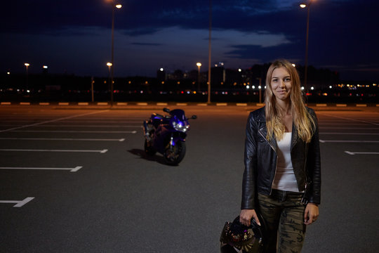 Positive beautiful young female in leather jacket posing in parking lot with safety helmet in her hands, looking at camera with smile, feeling excited while going for motorbike racing in night city