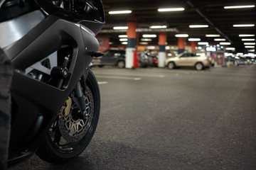 Cropped shot of blue motorbike in underground parking lot with cars parked in background. Close up of motorcycle rear tyre, blank asphalt with copy space for your text or promotional content