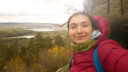 Girl in warm clothes with a scarf with a backpack on top of a rock mass makes a selfie on the background of autumn nature-a landscape with a lake. The brunette's hair is shaggy