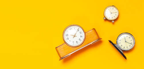 Three different Wooden retro alarm clock on bright yellow minimalistic background top view Flat Lay with copy space. The concept of time, morning, education.