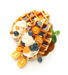 Tasty waffles with fruit, berries and cream on white background