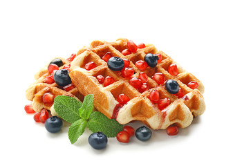 Tasty waffles with berries and pomegranate seeds on white background