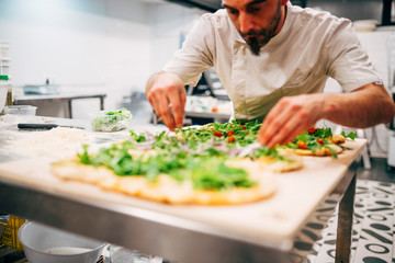 Man making a pizza in restaurant.