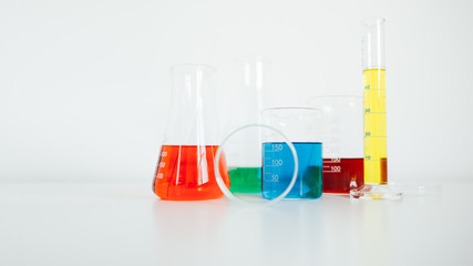 Laboratory equipment. Laboratory glassware with colorful liquids on white table