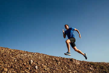 dynamic running uphill athlete runner on background of blue sky